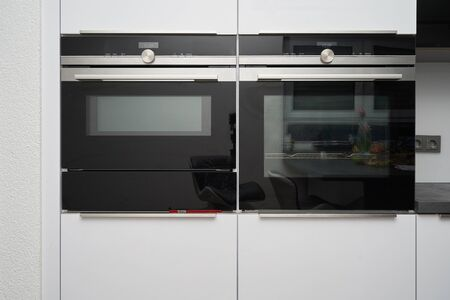 Microwave and metal-colored oven in white kitchen Reklamní fotografie