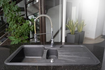 Black kitchen sink and chrome tap that can be pulled out for washing