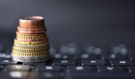 Euro coins lie in the form of a pyramid on a laptop keyboard in black, space for text