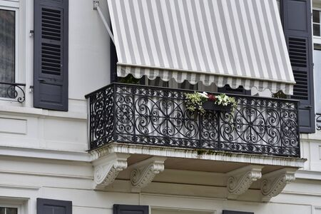 A beautiful wrought-iron balcony, covered with a sun shade and decorated with flowers in a flower pot