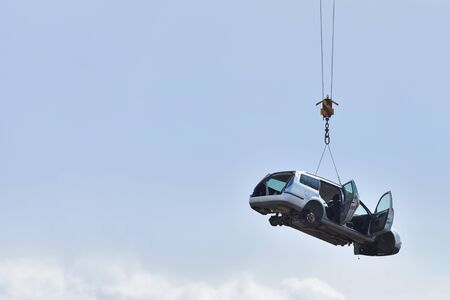 Discarded old car without wheels, lifted up by cables against a sky before recycling, with text space. Banco de Imagens
