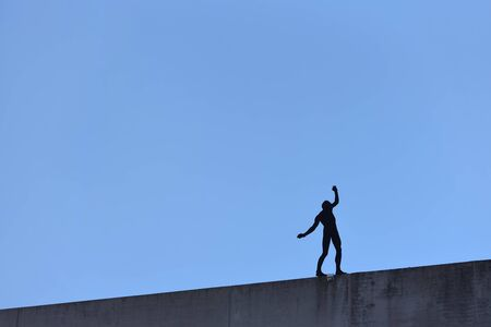 Artificial silhouette of a man who dangerously stands on the edge of a building balancing. Text space. The concept of risk and something dangerous