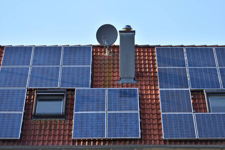 Solar panels installed on the roof of a house with tiles in Europe against the background of a blue sky. Archivio Fotografico