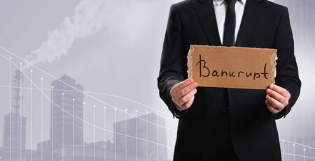 Business person holds a cardboard tablet with the word Bankrupt on the background of the plant. Bankrupt enterprise. 免版税图像