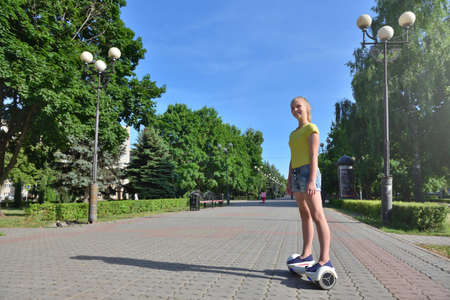 Happy girl child riding a hoverboard in summer park