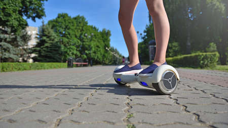 Girl child uses a hoverboard for riding in the park 스톡 콘텐츠