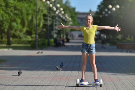 Happy teenager girl riding a hoverboard in a summer park with arms open