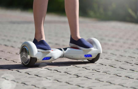 Legs of girl child and hoverboard while riding on the sidewalk in a park