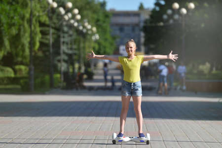 Joyful girl child riding a hoverboard in a summer park with arms extended 스톡 콘텐츠