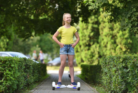 Smiling girl child riding a hoverboard having fun in a park on a background of trees