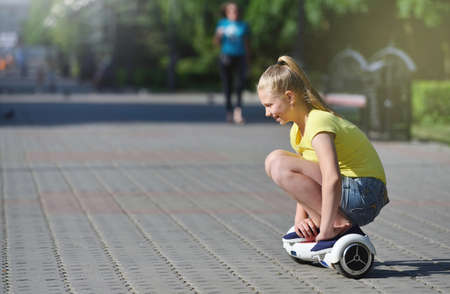 Happy girl child riding a hoverboard in summer park, authentic photo