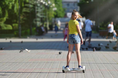 A girl child riding a hoverboard in a park and turning back and looking at the camera on a summer day 스톡 콘텐츠