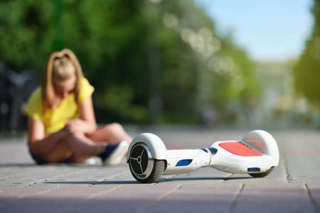 Girl child fell off a hoverboard and injured her knee while riding in a park