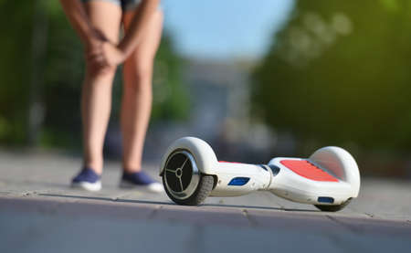 Girl child hurt her knee while falling off a hoverboard while riding in a park