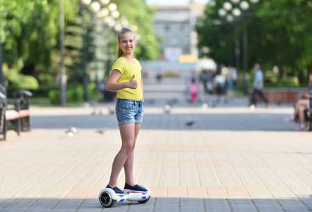 Girl child riding a hoverboard on a sunny day and showing a finger like looking at the camera.