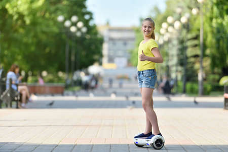 Girl child riding a hover board on a sunny day and showing a finger like looking at the camera 스톡 콘텐츠