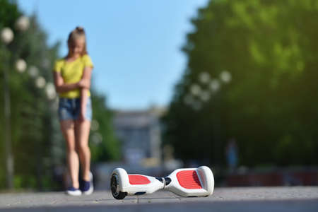 Girl child hurt her hand while falling from a hoverboard while riding in a park