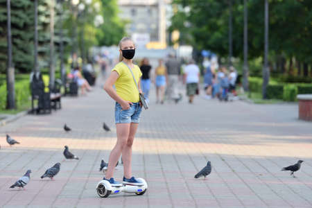 Girl child riding a hoverboard in a protective mask on the background of the park during the COVID-19 pandemic 스톡 콘텐츠