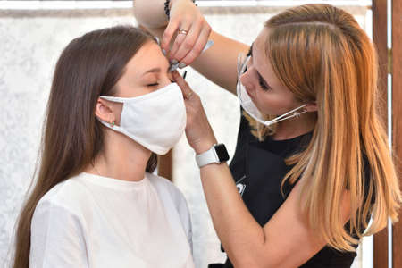 A young girl in a protective mask corrects her eyebrows in a beauty salon, social distancing during the COVID-19 pandemic Imagens