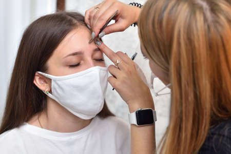 A young girl in a white protective mask at a beauty salon plucks her eyebrows before coloring, social distancing during the COVID-19 pandemic Imagens
