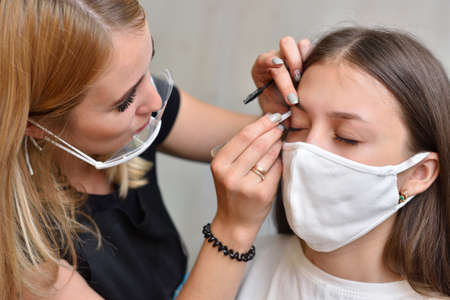 Eyebrow correction. A young brunette girl in a protective mask in a beauty salon corrects her eyebrows during the covid-19 pandemic