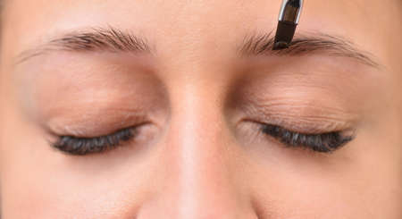 Eyebrow coloring young woman face close up