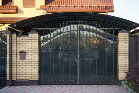 Black forged metal gates with decorative elements Stock Photo
