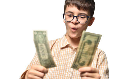 Boy teenager wondering looks at money in his hands on white isolated background