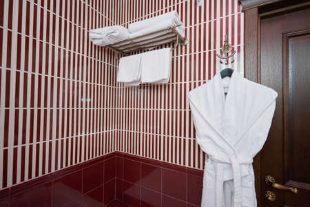 White towels and bathrobe in the bathroom in the hotel