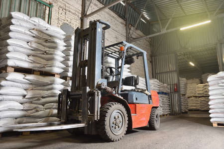 A forklift stands in a warehouse next to pallets with full bags