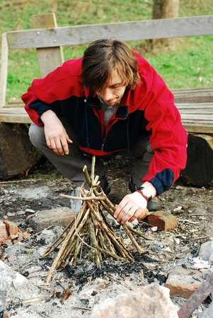 Young man lighting fire outdoors