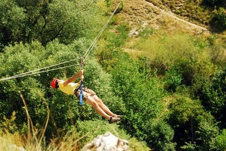 zip: man descending on a zip-line (flying fox)