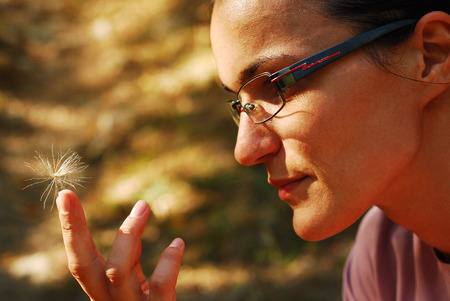 fluffy tuft: portrait of a woman holding a thistle seed