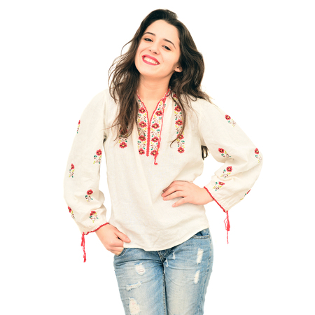 pretty young woman wearing a romanian traditional shirt over white background Stock Photo