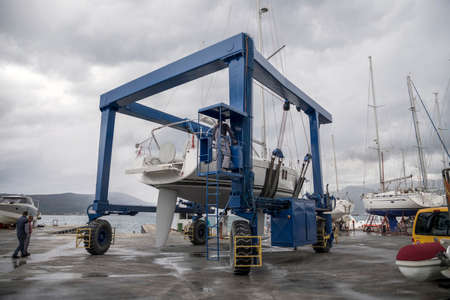 Tivat, Montenegro, Apr 29, 2019: Sailing yacht transporting in the sea by marina mobile crane Editorial