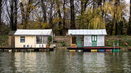 Two raft houses moored to the riverbank 版權商用圖片