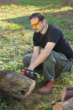 Man cutting wood with electric saw photo