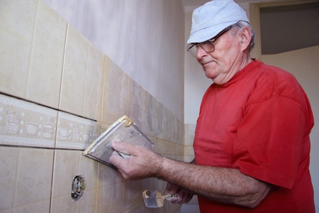 affix: Senior man decorating with ceramic tiles