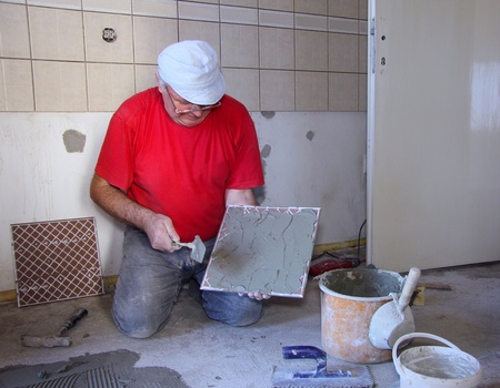 modernization: Senior man decorating with ceramic tiles