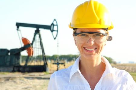 yacimiento petrolero: Sonriendo Ingeniero de sexo femenino en un campo petrol�fero