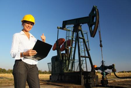yacimiento petrolero: Sonriendo Ingeniero de sexo femenino en un campo petrolífero