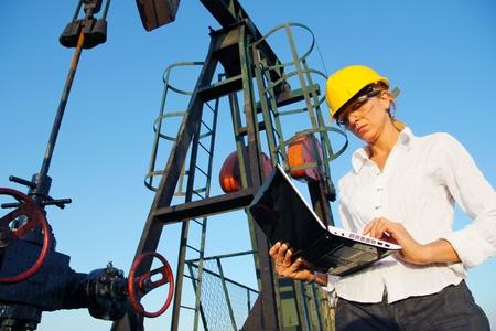 yacimiento petrolero: Empresaria con un cuaderno en un campo petrol�fero