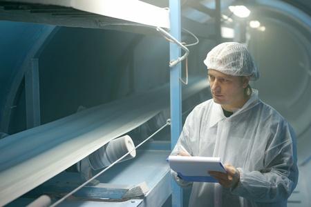 cinturon seguridad: Trabajador controla el az�car en la l�nea de producci�n en una f�brica