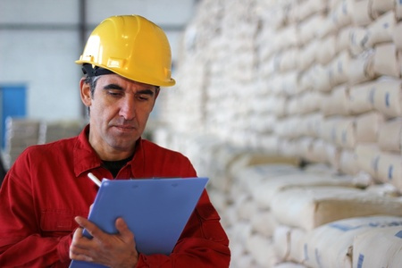 agriculture industry: Worker writing results in factory, sacks in sugar factory Stock Photo