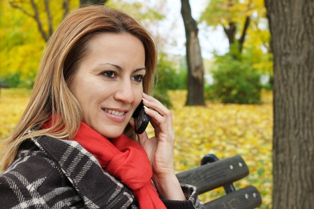 Woman in Park talking on a mobile phone photo
