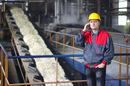 Industrial worker talking on cell phone at the factory for the production of food photo
