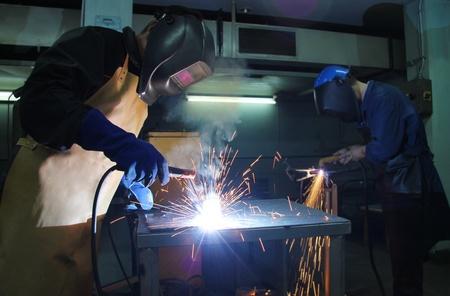 hard work: Steel Workers welding, grinding, cutting in metal industry