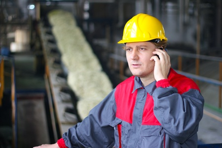 Industrial worker talking on cell phone in food industry Imagens