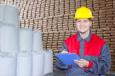 Happy worker in warehouse writing on clipboard photo