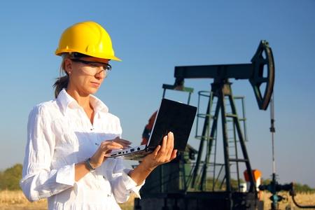 yacimiento petrolero: Ingeniero de sexo femenino en un campo petrolífero de trabajo con ordenador portátil